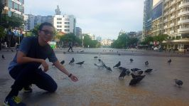 memberi makan burung di Nguyen Hue Street